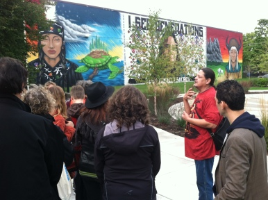 Alan Gross discusses the mural in the background, which illustrates the Ojibwe origin story.